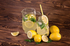 A huge jug and glass full of fresh summer lemonade with yellow, ripe, and juicy lemon and fresh green mint on a dark wooden table. stock photo