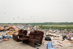 Huge landfill of trash and recycles with old couch in forefront Royalty Free Stock Image