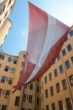 Huge Latvian national flag hang on former KGB headquarters in Riga (The Corner House), the Latvian Museum of the Occupation. Royalty Free Stock Photography