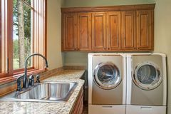 Huge laundry room with white washer and dryer. Brown wood cabinets, granite countertop framing the sink with black faucet. Northwest, USA stock image