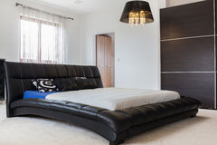 Huge leather bed in bedroom Royalty Free Stock Image