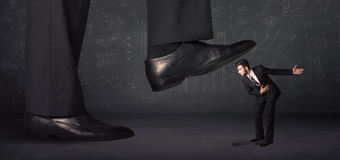 Huge leg stepping on a tiny businnessman concept stock photo