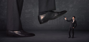 Huge leg stepping on a tiny businnessman concept Royalty Free Stock Photography