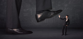 Huge leg stepping on a tiny businnessman concept Royalty Free Stock Photos