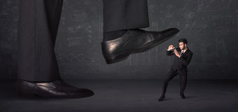 Huge leg stepping on a tiny businnessman concept Royalty Free Stock Photo