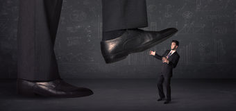 Huge leg stepping on a tiny businnessman concept Stock Photo