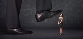 Huge leg stepping on a tiny businnesswoman concept Royalty Free Stock Photography