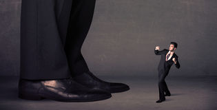 Huge legs with small businessman standing in front concept Stock Photos