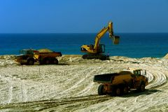 Huge machines. Machines working at beach Royalty Free Stock Images