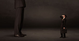Huge man with small businessman standing at front concept Royalty Free Stock Photos