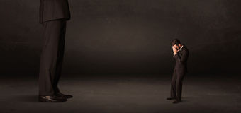 Huge man with small businessman standing at front concept Stock Image