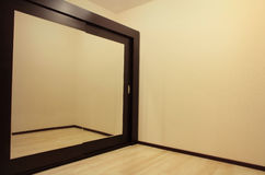 Huge mirror wardrobe in empty room. Stock Photography