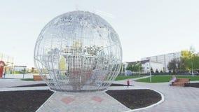 Huge modern glass plates globe sculpture on square. Kazan, Tatarstan Russia - May 3 2018: Huge modern made of glass plates transparent globe sculpture with stock footage