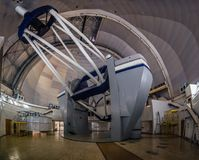 Huge modern professional astrophysical telescope under dome of observatory.  stock photos