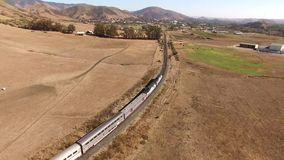 Huge modern urban passenger train moving through dry sand steppe canyon hill desert of amazing 4k aerial drone landscape. Huge modern urban passenger train stock video