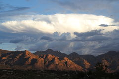 Huge Monsoon clouds over the  Pusch Ridge mountains at sunset in Tucson Arizona winter landscape. Mountains desert landscape. Mountain landscape at sunset. Pusch Royalty Free Stock Images
