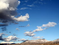 Huge monsoon clouds in winter over the snow covered Santa Catalina mountains at sunset in Tucson Arizona. Mountains.  tucson mountains. Tucson Arizona. Big sky Royalty Free Stock Photo