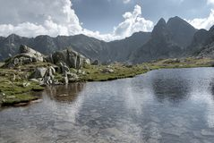 Huge mountain lake among high peaks and white summer clouds. In Retezat, Romania Stock Image