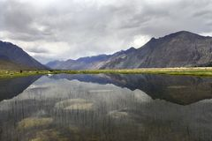 A huge mountain lake in the Nubra valley, dark massifs of the mountains go into the distance, the water reflects the gray clouds,. Huge mountain lake in the Royalty Free Stock Photo