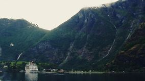 Huge mountains covered by green woods at river. Cruise liner at port. Nature. Landscape. Seagull stock video footage