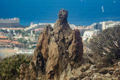 Huge mystical lava rock surraunded by canarian endemic plants. Los Cristianos view from Guaza mountain. Tenerife, Canary Islands. Spain royalty free stock photo