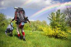 Huge novice backpack in the mountains. An outdated way of traveling is a huge uncomfortable backpack stuffed with cumbersome heavy equipment. Now things in the Royalty Free Stock Images
