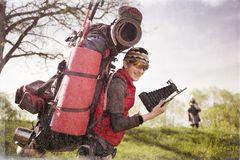 Huge novice backpack in the mountains. An outdated way of traveling is a huge uncomfortable backpack stuffed with cumbersome heavy equipment. Ancient camera- as Royalty Free Stock Photos