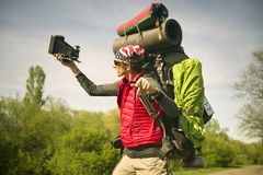 Huge novice backpack in the mountains. An outdated way of traveling is a huge uncomfortable backpack stuffed with cumbersome heavy equipment. Ancient camera- as Royalty Free Stock Image