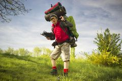 Huge novice backpack in the mountains. An outdated way of traveling is a huge uncomfortable backpack stuffed with cumbersome heavy equipment. Ancient camera- as Royalty Free Stock Photography
