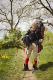 Huge novice backpack in the mountains. An outdated way of traveling is a huge uncomfortable backpack stuffed with cumbersome heavy equipment. Now things in the Stock Photos