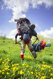 Huge novice backpack in the mountains. An outdated way of traveling is a huge uncomfortable backpack stuffed with cumbersome heavy equipment. Now things in the Stock Photo