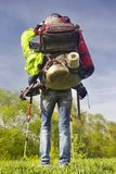 Huge novice backpack in the mountains. An outdated way of traveling is a huge uncomfortable backpack stuffed with cumbersome heavy equipment. Now things in the Stock Images