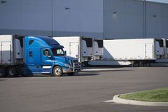 Big rig semi truck with refrigerated semi trailer standing for l. A huge number of big rig semi trucks are loaded and unloaded in the docks of huge warehouses stock image