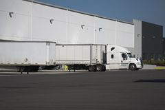 White big rig semi truck with dry van semi trailer stand in ware. A huge number of big rig semi trucks are loaded and unloaded in the docks of huge warehouses royalty free stock image