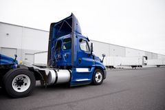 Big rig day cab blue semi truck driving to warehouse dock for pi. A huge number of big rig semi trucks are loaded and unloaded in the docks of huge warehouses royalty free stock image