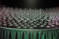 Huge number of empty clean wine glasses on the table during the Banquet. Illuminated by neon lights royalty free stock image