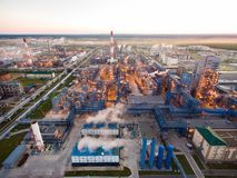 A huge oil refinery with metal structures, pipes and distillation of the complex with burning lights at dusk. Aerial Stock Photo