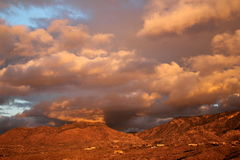 Huge orange monsoon clouds over the deep amber mountains at sunset  in Tucson Arizona. Desert mountain sunset. Sunset heavily saturated with color. Dramatic red Royalty Free Stock Image