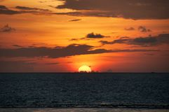 The huge orange semicircle of the sun sets behind the water, the red sky with gray clouds, the sunset in the Maldives. Huge orange semicircle of the sun sets Stock Image