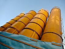Huge orange silos for building materials. Huge silos filled with concrete, sand, or other building materials. Viewed from bottom in front of a blue sky stock images