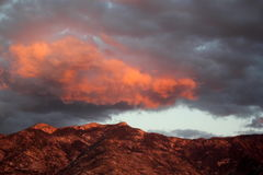 Huge Orange sunset cloud over the mountains in Tucson Arizona. Isolated orange cloud. Gigantic orange cloud at sunset. Orange mountain sunset. Colorful mountain Royalty Free Stock Photos