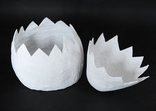 Huge papier mache egg is uncovered in two parts on a black background Stock Photos