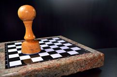 Huge pawn. Chessboard and huge lone pawn on a black background Stock Photography