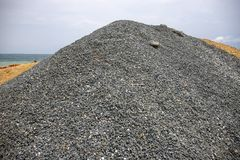 Huge pile of grey gravel on coast. Construction site material. Big gravel heap outdoor. Construction supply closeup. Small gravel stones. Coastal road royalty free stock photo
