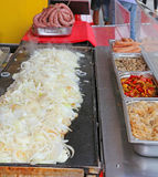 Huge pile of onions and sausage in the street stall Stock Photo