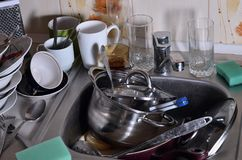 A huge pile of unwashed dishes in the kitchen sink and on the co. Untertop. A lot of utensils and kitchen appliances before washing. The concept of daily cooking royalty free stock photography