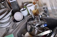 A huge pile of unwashed dishes in the kitchen sink and on the co. Untertop. A lot of utensils and kitchen appliances before washing. The concept of daily cooking stock image