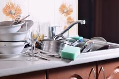 A huge pile of unwashed dishes in the kitchen sink and on the co. Untertop. A lot of utensils and kitchen appliances before washing. The concept of daily cooking stock photo