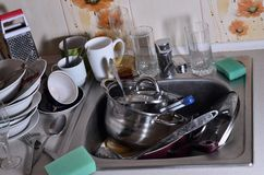 A huge pile of unwashed dishes in the kitchen sink and on the co. Untertop. A lot of utensils and kitchen appliances before washing. The concept of daily cooking royalty free stock images