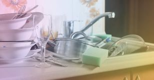 A huge pile of unwashed dishes in the kitchen sink and on the co. Untertop. A lot of utensils and kitchen appliances before washing. The concept of daily cooking royalty free stock photo